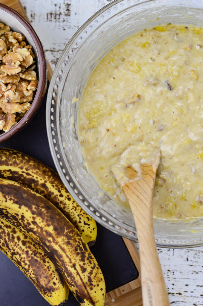 A bowl of banana nut bread batter with a wooden spoon in it. Three ripe bananas and a bowl of walnuts sit next to it.