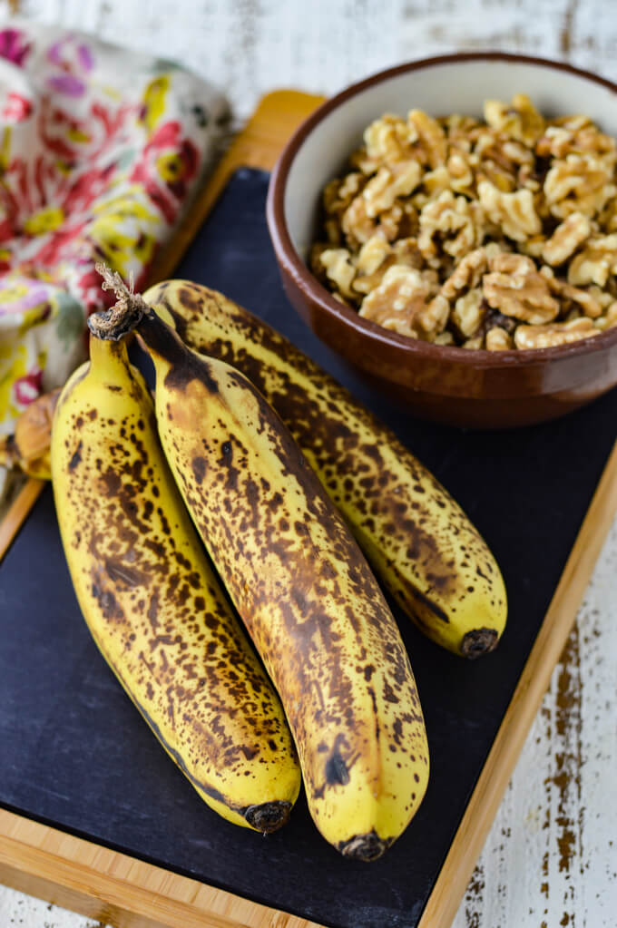 Four ripe bananas sit on a black cutting board with a bowl of walnuts next to them.
