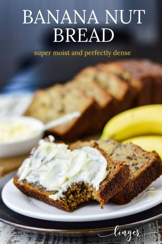 Two slices of banana nut bread sit on a white plate. One has butter smeared on it and a bite taken out. Bananas, butter and more slices of bread sit in the background.