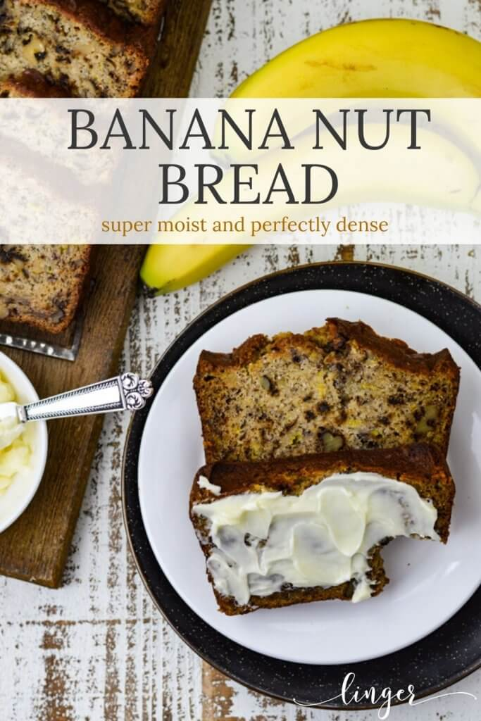 Two slices of banana nut bread sit on a white plate. One has butter smeared on it and a bite taken out. Bananas, butter and more slices of bread sit on a wooden cutting board next to them.