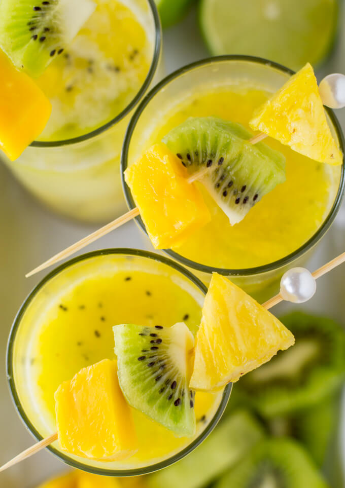 An overhead shot of three Tropical Cocktails with Coconut Rum garnishes with pineapple, mango and kiwi on a cocktail skewer. Fruit is blurred down below the drinks.