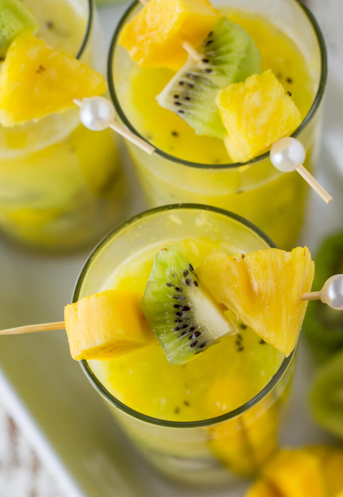 Three glasses of tropical cocktails garnished with pineapple, kiwi and mango sit on a white serving tray. Fresh fruit sit next to the glasses.