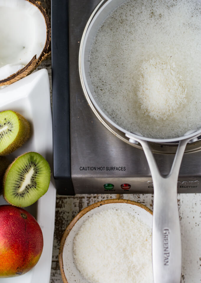 A pan of water with shredded coconut in it. A broken coconut, kiwi and mango sit next to the pan.