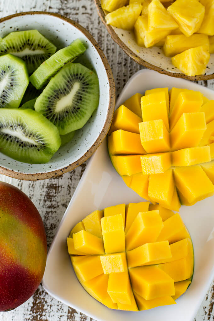 A mango shown how to cut it into cubes is shown in the photo. A bowl of kiwi, cubed pineapple, and a whole mango sit next to the cubed mango.
