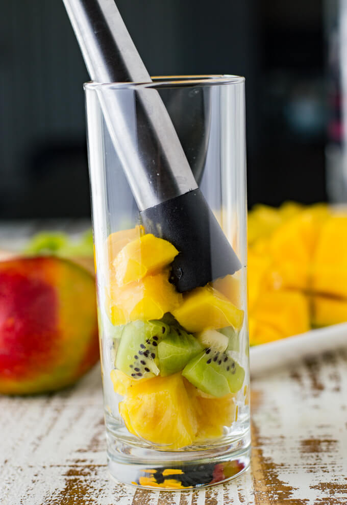 A high ball glass holds cubed pineapple, mango and kiwi with a muddler stuck in it.