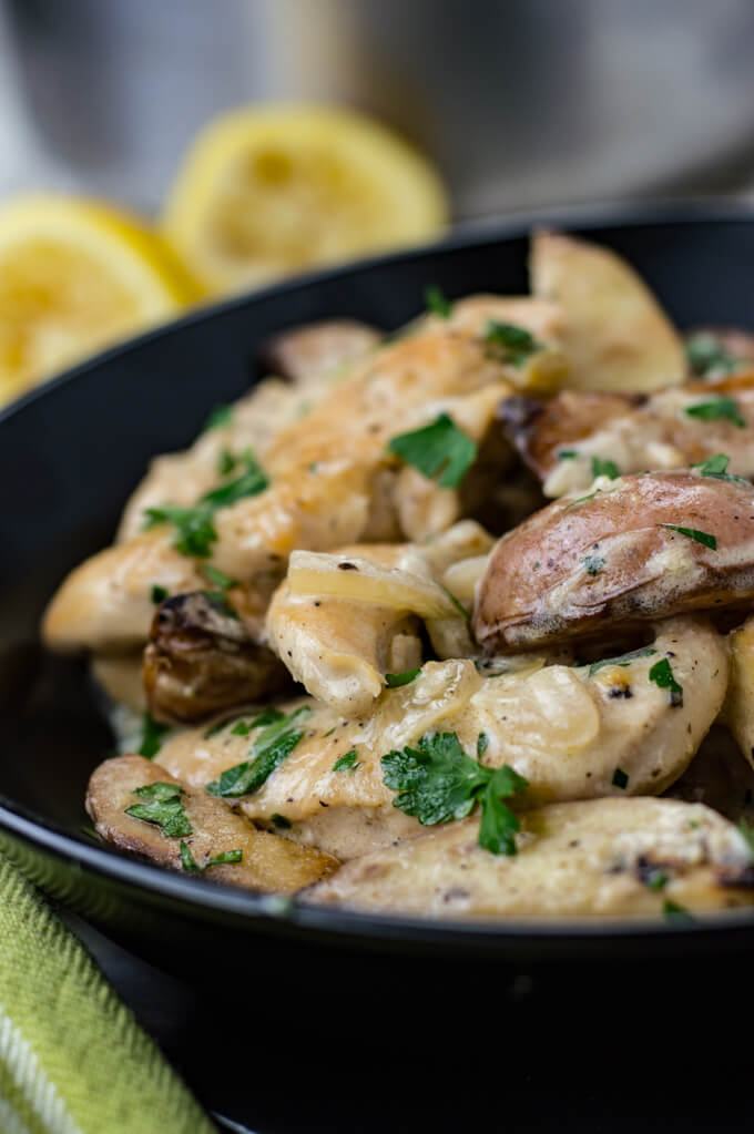 A creamy lemon chicken dish is in a black bowl with squeezed lemons in the background and a green napkin next to the bowl.