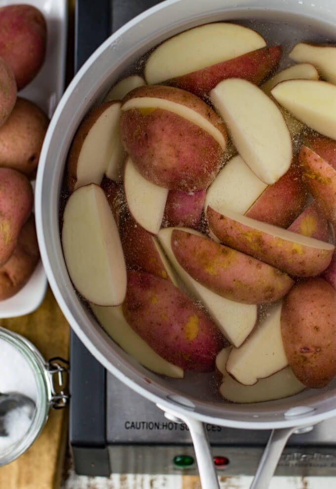 Raw potato wedges sit in a pan and covered with water. Whole potatoes and a jar of salt sit next to the pan.