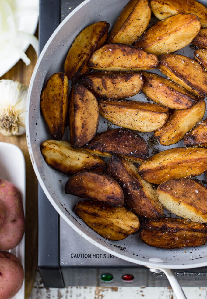 A skillet with fried potato wedges. Whole red potatoes, garlic bulbs and sliced onions sit next to the skilled.
