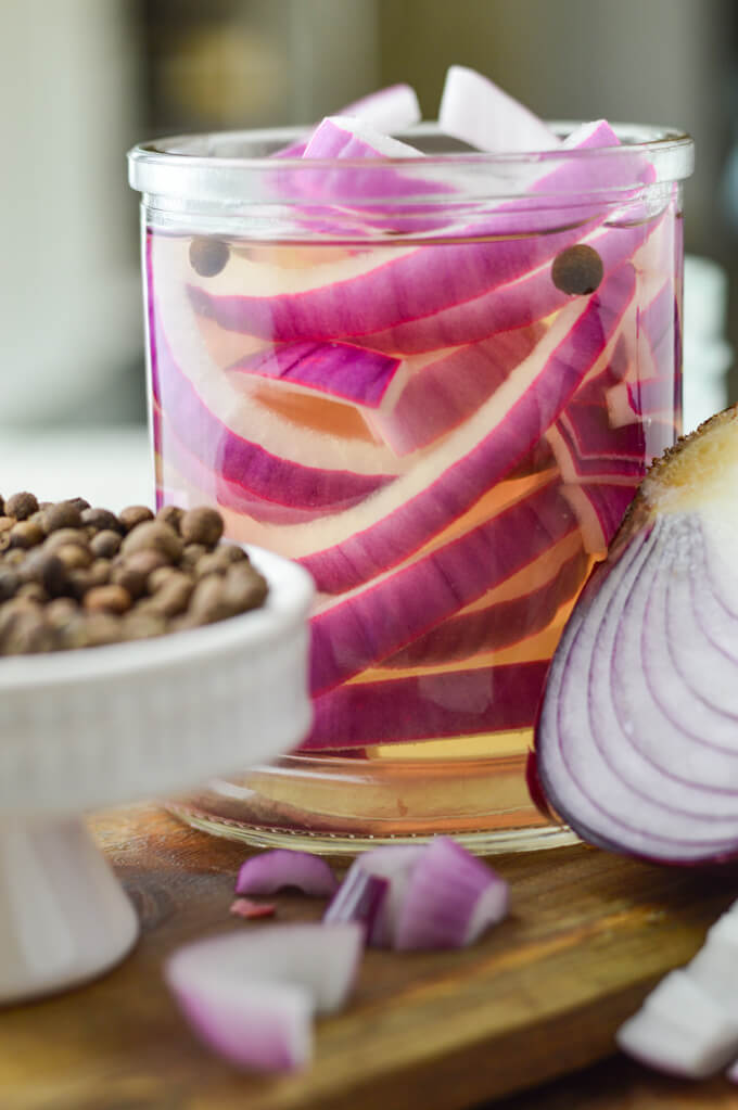 A jar of pickled onions sit on a wooden tray. Allspice berries and a half cut red onion are in the forefront of the photo.
