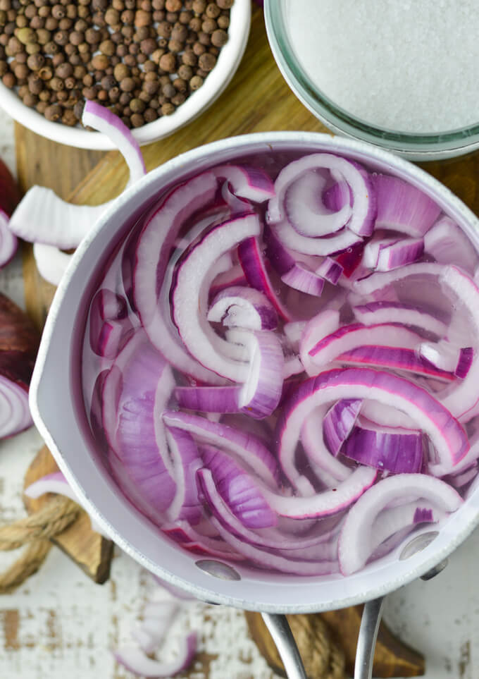 A pan of water holds slices of red onions. Allspice berries and sugar sit next to the pan.