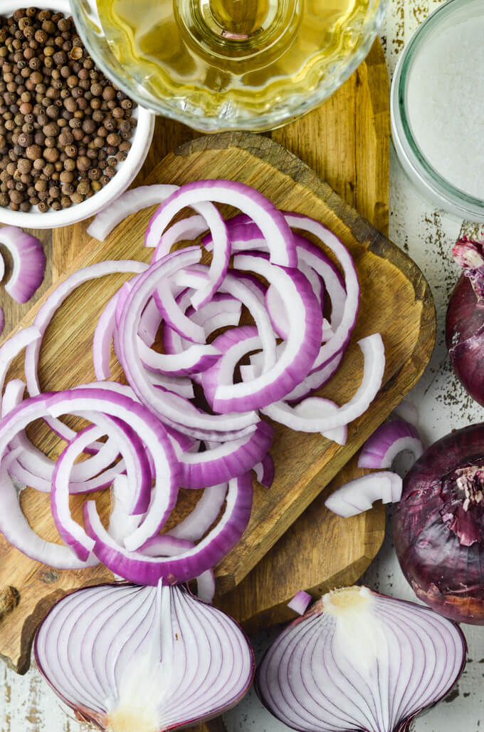 A cutting board holds slices of red onions. Allspice berries are in a bowl beside them. A clear bowl of vinegar and a jar of sugar are in the corner of the photo.