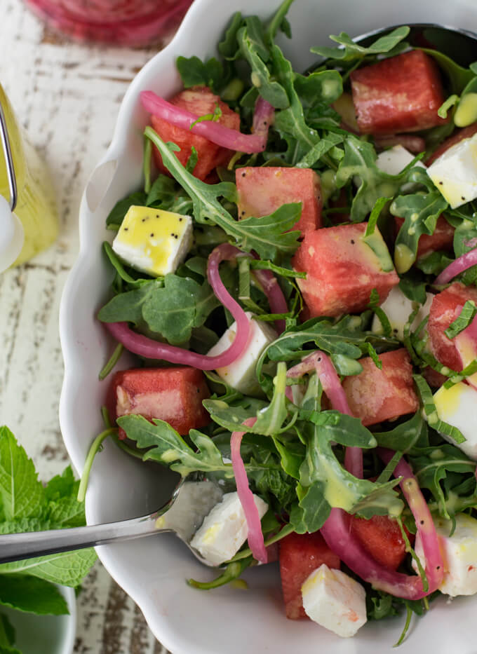 Pickled Red Onions top a watermelon arugula salad.