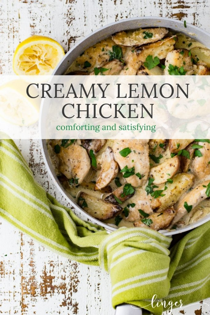 A pan of creamy lemon chicken with parsley sprinkled on top. A green and white striped napkin sits next to it. And 2 squeezed lemon halves are next to the pan.