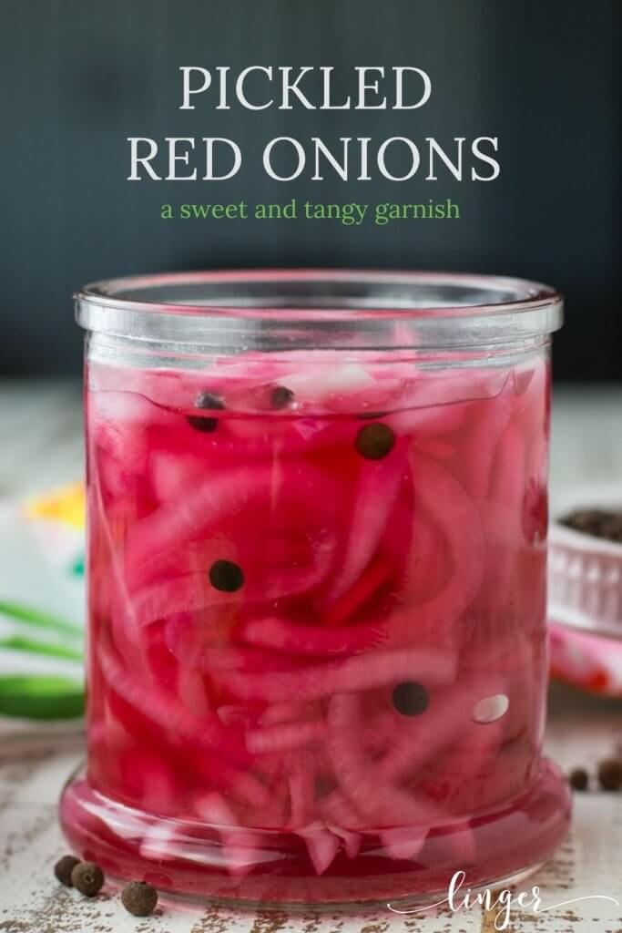 A jar of pickled red onions with a colorful napkin & a bowl of allspice berries are in the background.