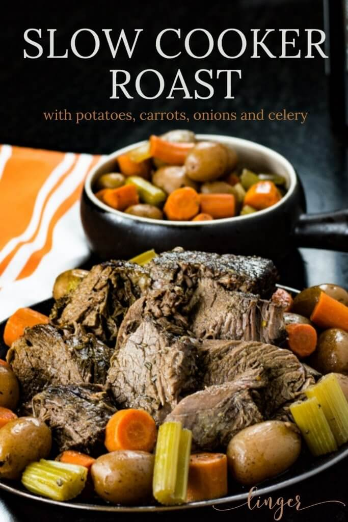 A plate of sliced cooked pot roast sit on a bed of carrots, potatoes, celery and onions. A bowl fo the vegetables sit in the background.