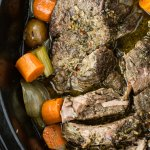 A cooked pot roast in a ceramic crock pot with carrots, potatoes, celery and onions.
