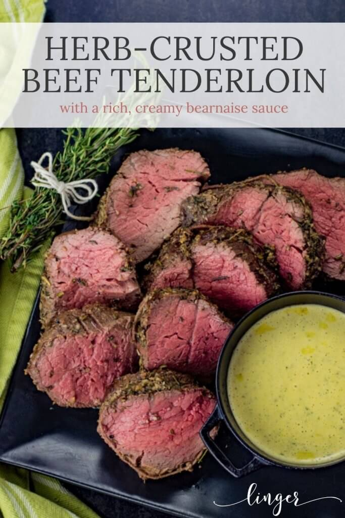 Sliced beef tenderloin cook rare sit on a black plate with a bundle of rosemary in the top left corner. A bowl of bearnaise sauce sits next to the slices of tenderloin.