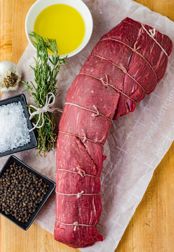 A raw beef tenderloin that is tied and sitting on parchment paper with salt, pepper, a bundle of rosemary and thyme and a bowl of melted butter.