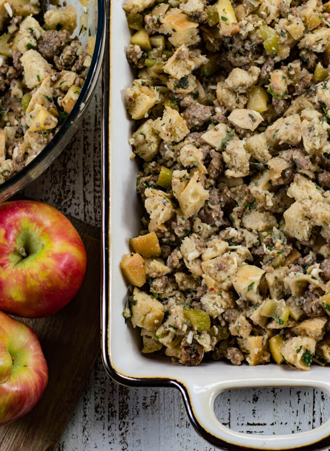 Uncooked homemade stuffing with apples and sausage in a white casserole dish. A bowl of the stuffing and two apples sit next to the pan.