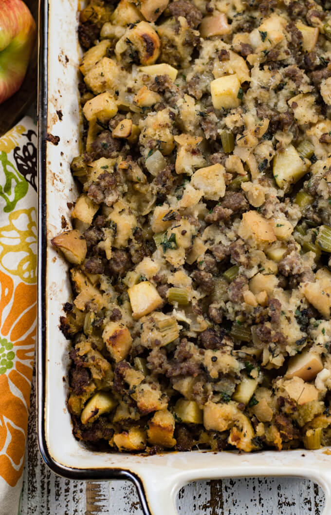 Homemade stuffing with apples and sausage baked in a white casserole dish. A colorful napkin sits next to the pan.