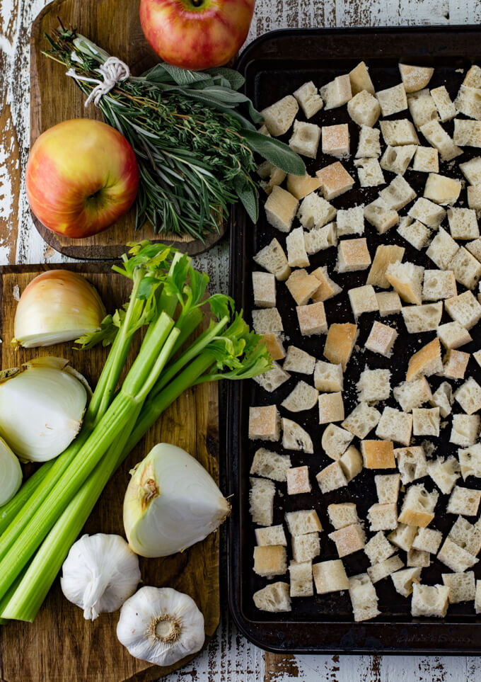 Cubes of bread on a baking sheet with apples, fresh herb, celery and onions sitting next to the pan.