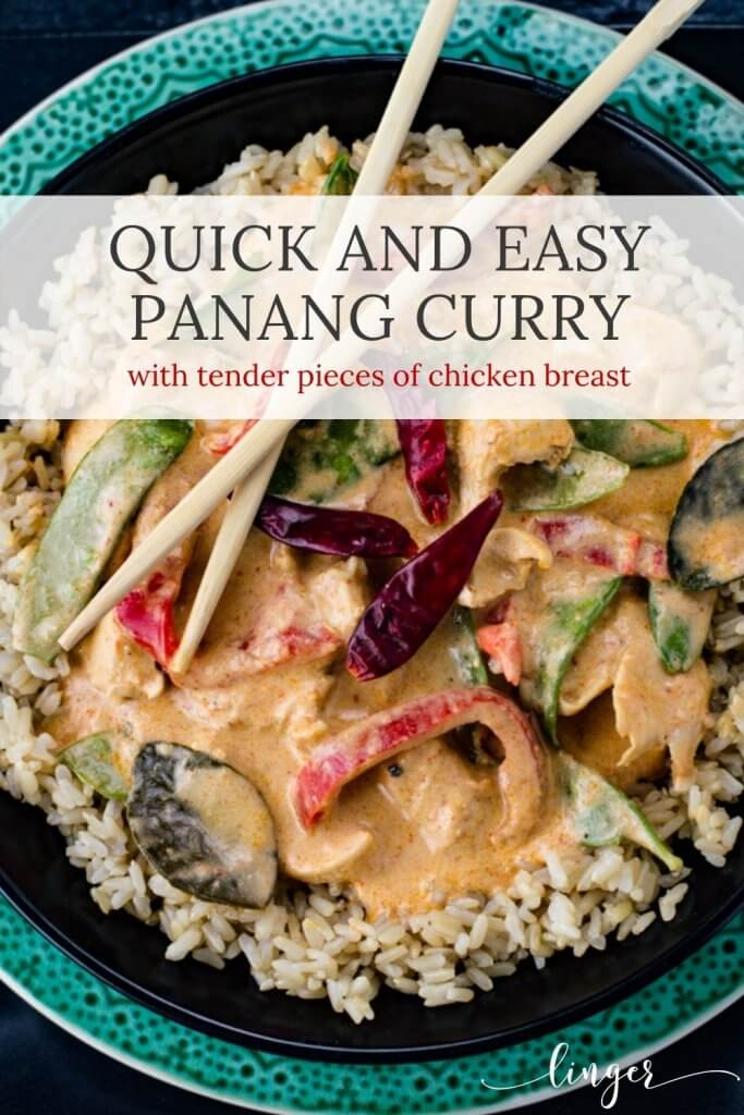 Chicken Panang curry sits on a bed of brown rice in a black bowl that sits on a green plate.