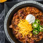 A bowl of homemade chili with ground turkey. Shredded cheese, a dollop of sour cream and sliced jalapenos are garnished on top. Bowls of cheese and jalapenos sit in the corner of the photo.