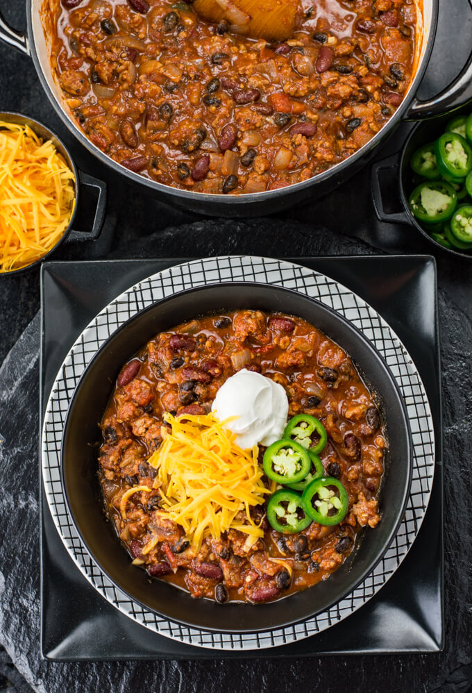 A black bowl of turkey chili sits on a black and white checkered plate that sits on a large black plate. Shredded cheese, a dollop of sour cream and sliced jalapenos sit on top the chili. A Dutch oven with chili is at the top of the photo with bowls of more cheese and jalapanos.