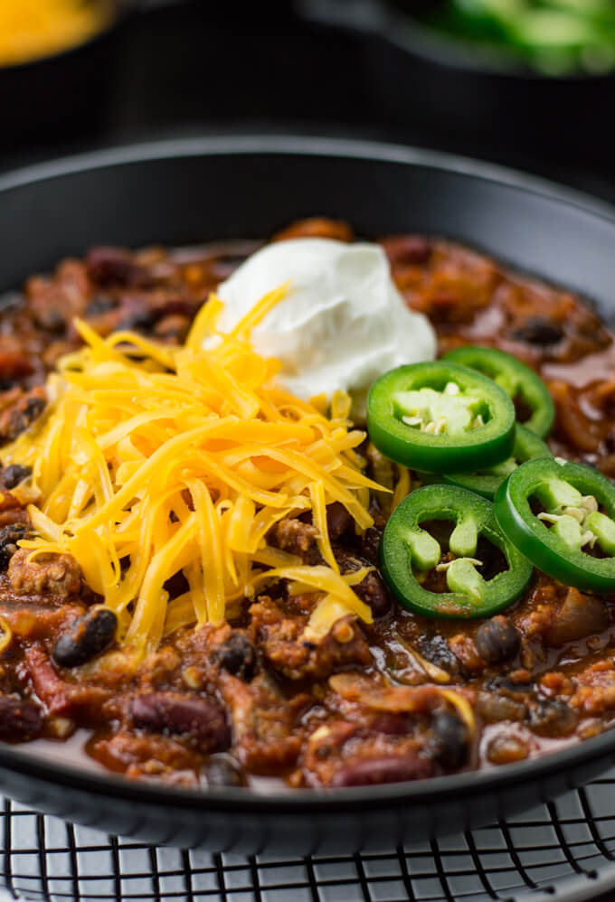 A black bowl of homemade turkey chili sits on a black and white checkered plate. Shredded cheese, a dollop of sour cream and sliced jalapenos sit on top the chili. Bowls of cheese and jalapenos are blurred in the background.