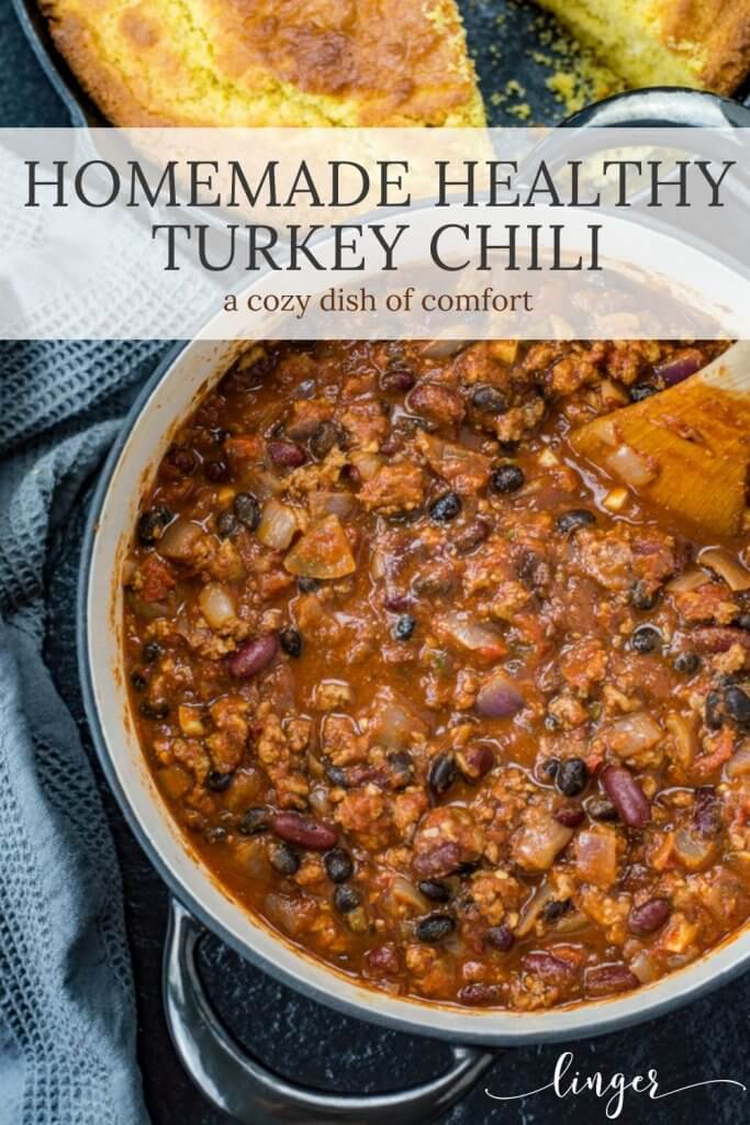 A Dutch oven of homemade turkey chili with a wooden spoon in the chili.