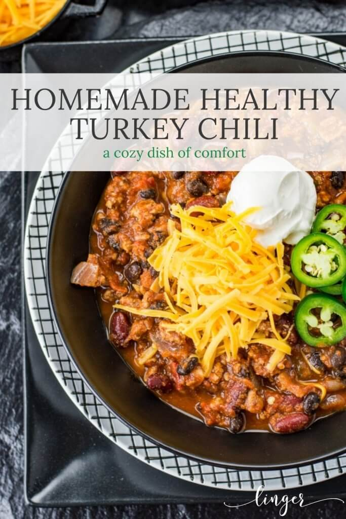 A bowl of homemade chili with ground turkey. Shredded cheese, a dollop of sour cream and sliced jalapenos are garnished on top. Bowls of cheese sits in the corner of the photo.