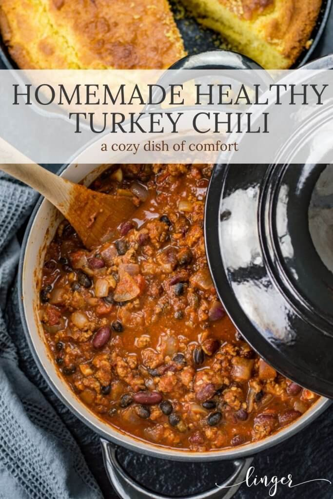 A Dutch oven of homemade turkey chili with a wooden spoon in the chili. A black lids is partially over the chili. A cast iron skillet has homemade cornbread with a slice taken out. It sits next to the chili.