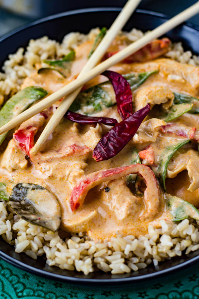 A close-up photo of a dish of chicken panang curry sitting on brown rice. It's loaded with onions, red bell peppers and snow peas. Three dried red chili peppers garnish the top.