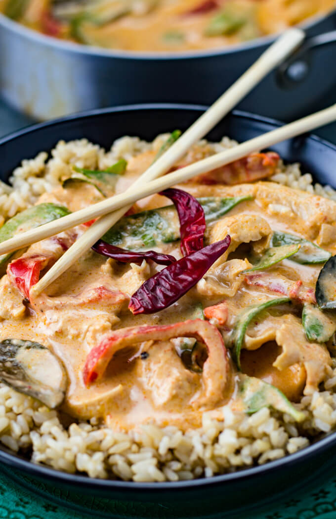 Chicken Panang curry sits on a bed of brown rice in a black bowl that sits on a green plate. A pan of the curry is blurred in the background.