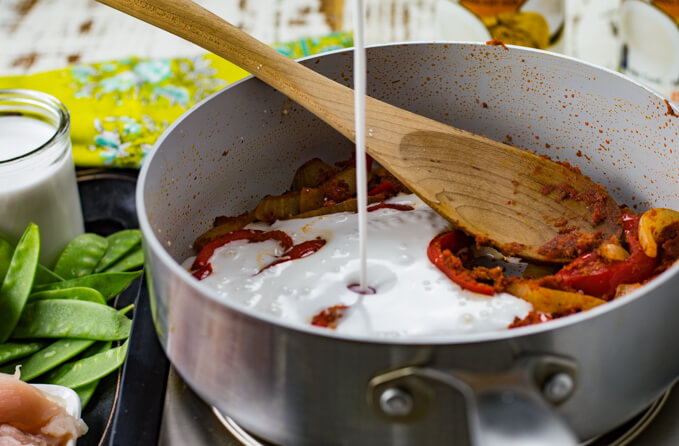 A pan of sautéd vegetables and a wooden spoon. Coconut milk is being poured into the pan.