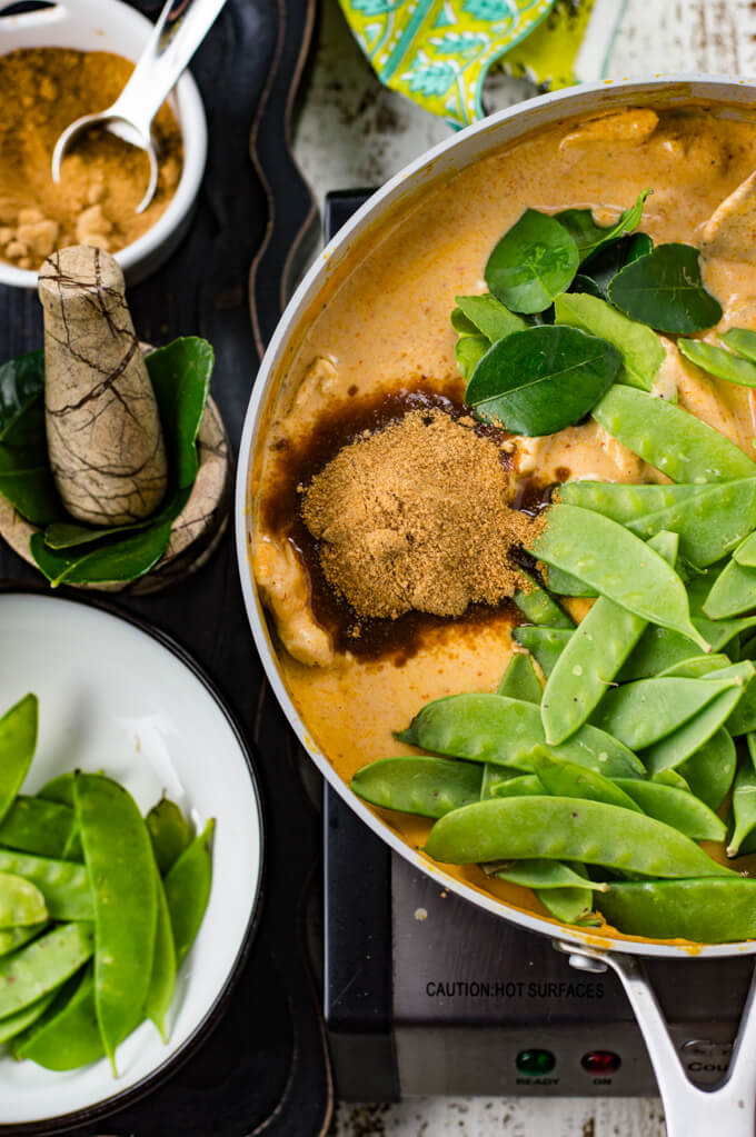 A pan of panang curry sauce with coconut sugar, kaffir lime leaves and snow peas on top of the sauce.