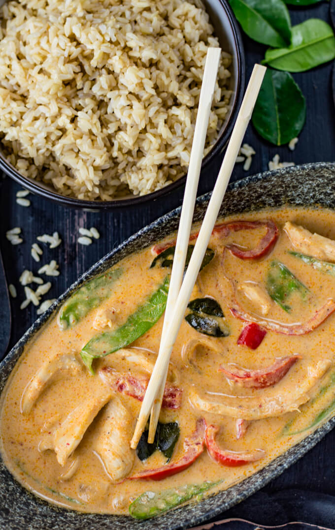 A gray dish with chicken panang curry and chopstick resting on the sauce. A bowl of brown rice sits next to it with some rice & kaffir leaves scattered around.