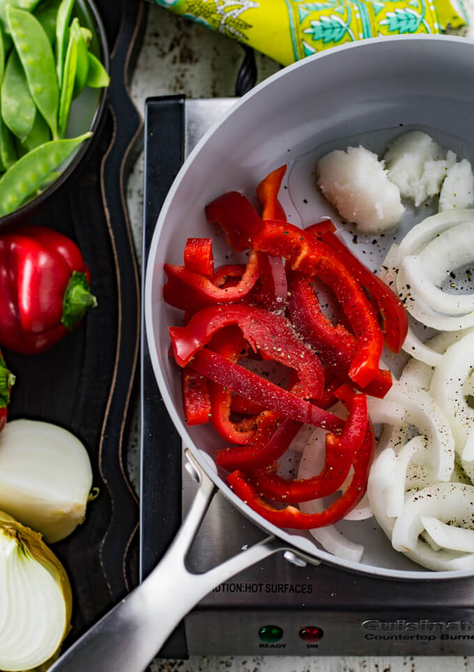 A pan of sliced red bell peppers, onions and coconut oil. Snow peas, red bell pepper and onion sit next to the pan along with a green napkin.