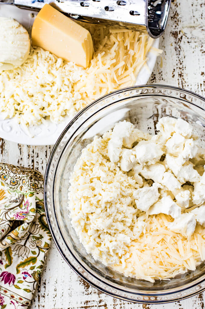 A clear mixing bowl with shredded mozzarella and parmesan and goat cheese. A white bowl sits next to it with a grater and the cheeses. A green, tan and purple napkin sit net to it.