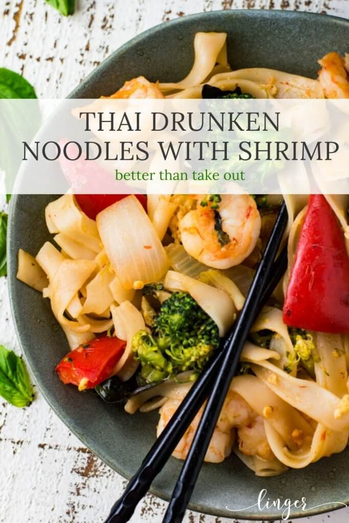 A gray bowl of Thai Drunken Noodles with broccoli, red peppers and onions. Black chop sticks sit in the dish.