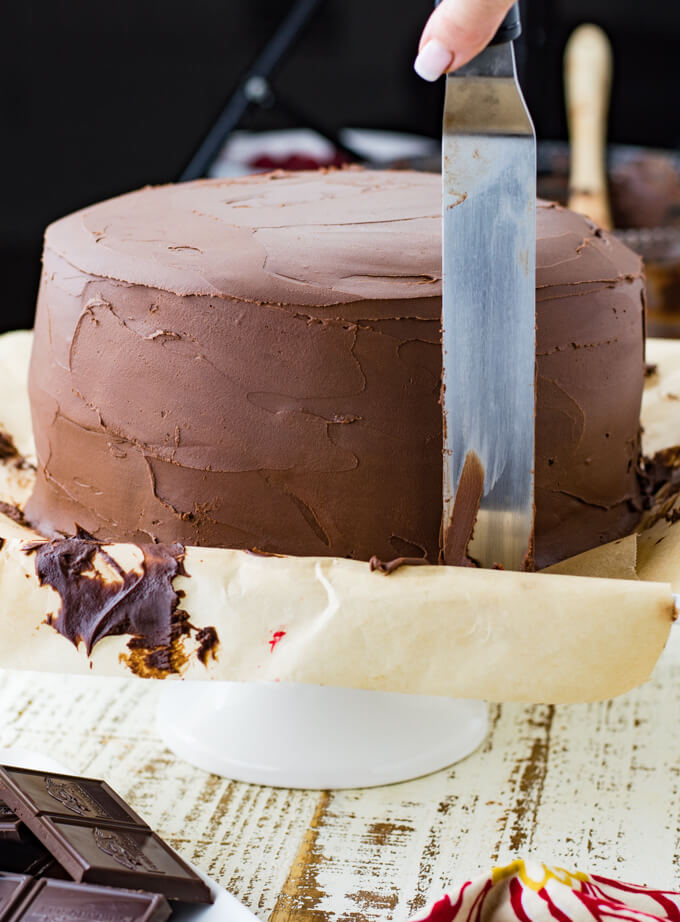 A layered chocolate cake sitting on parchment paper that is on a cake plate. A cake spatula is used to frost the cake.