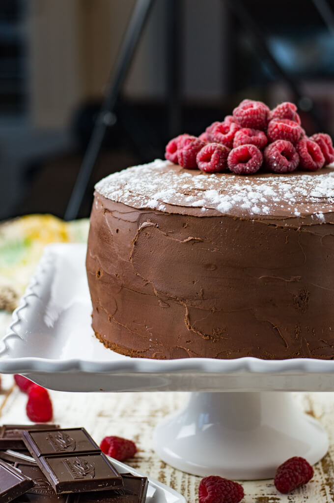 A layered chocolate raspberry cake sitting on a cake plate, sprinkled with powdered sugar and garnished with fresh whole raspberries.