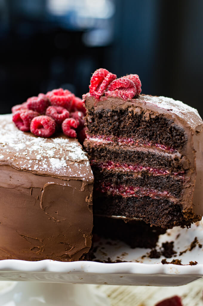 A layered chocolate raspberry cake with a piece being pulled away from it.