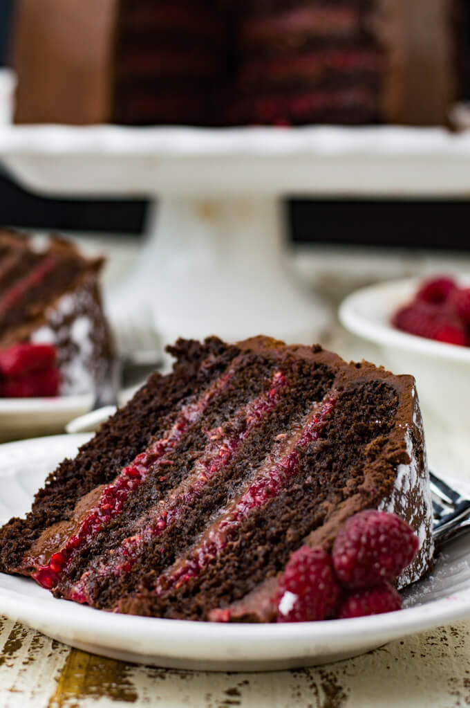 A piece of 4 layer chocolate raspberry cake sits on a white place. The cake sits in the background.