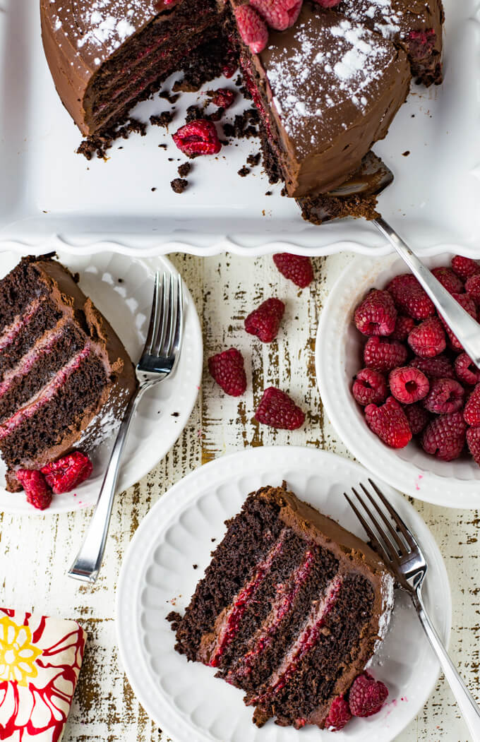 Two pieces of 4 layered chocolate cake with a raspberry filling. The cake sits on a cake plate with slices taken out. A bowl of red raspberries sit next to the cake. A few raspberries are scatter around. A colorful napkin is in the corner of the photo.
