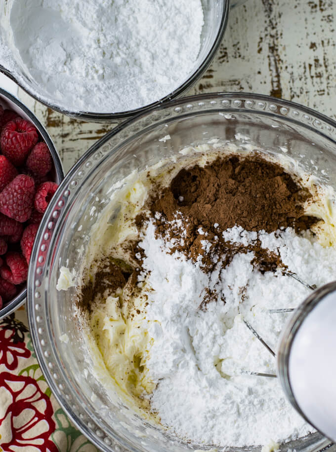 A mixing bowl with ingredients for chocolate icing: powdered sugar, butter, cream cheese, and cocoa. Bowls of powdered sugar and fresh raspberries sit next to the bowl.