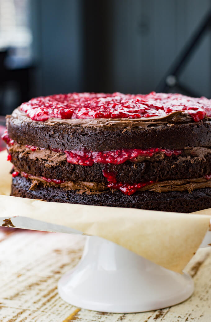 A side photo of a chocolate cake with layers of chocolate frosting and raspberry filling.