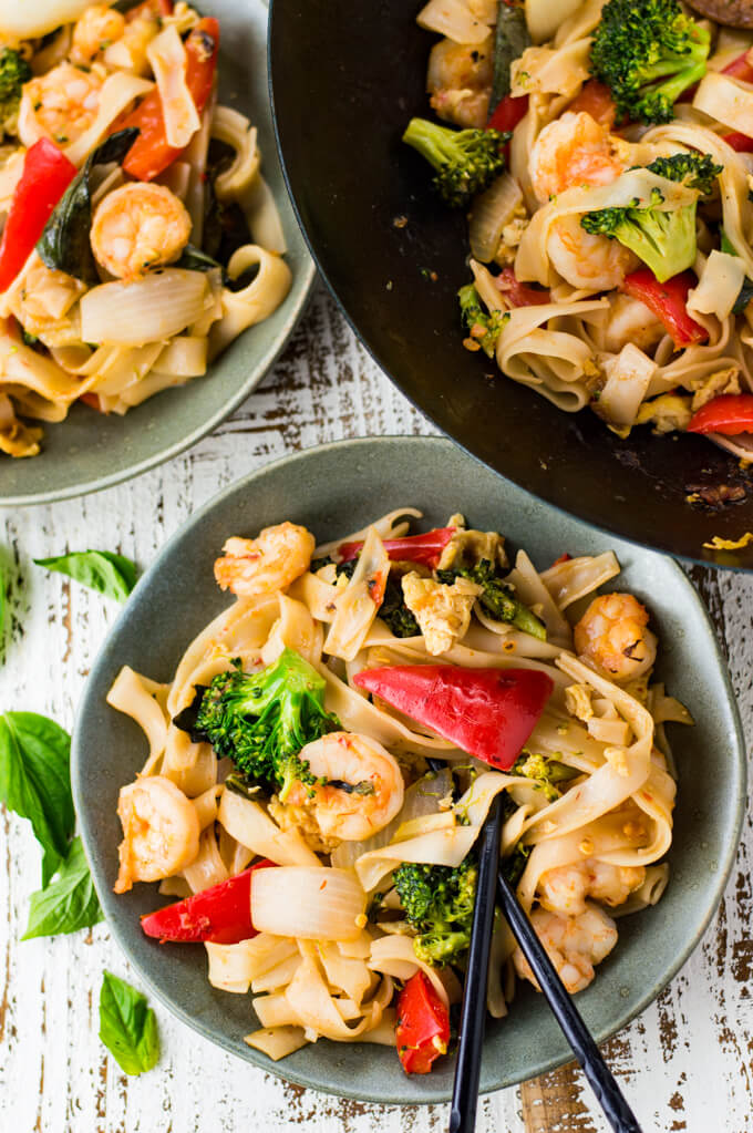 A gray bowl of Thai Drunken Noodles. Another bowl and a wok of the same is at the top of the photo. A few Thai Basil leaves lie next to the bowl.