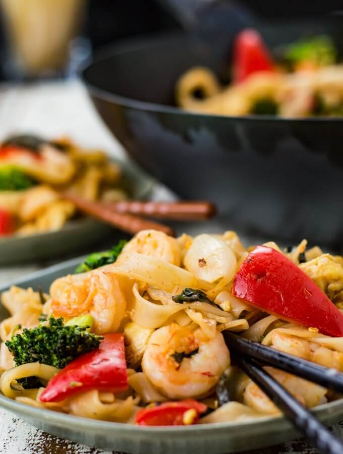 A front view of a bowl of Thai Drunken Noodles with black chopsticks. Another bowl and a wok with the same is blurred in the background.