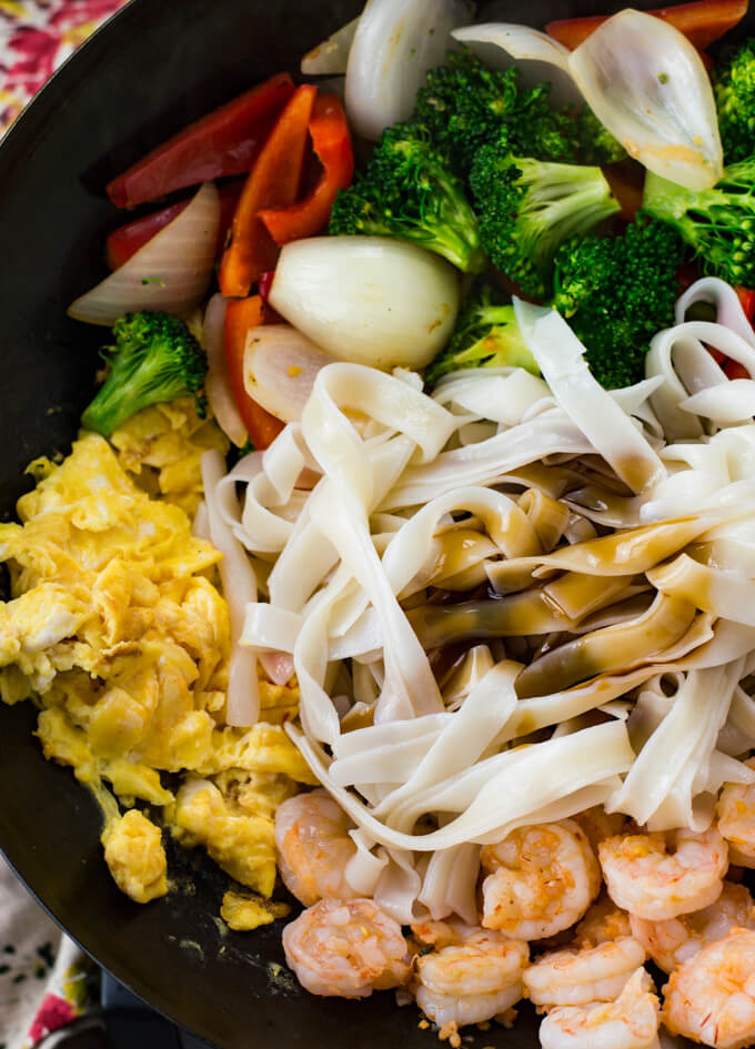 A wok of scrambled eggs, sauteed vegetables, cooked shrimp, cooked rice noodles and sauce.